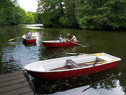 People rowing boats in lake at Tiergarten park in Berlin Germany