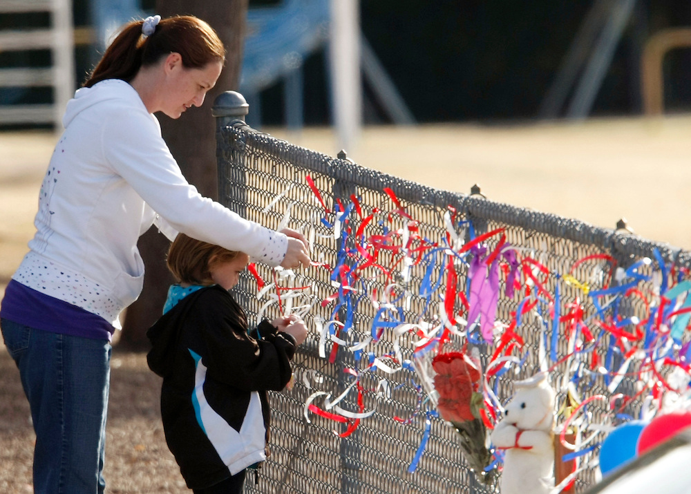 A student at Mesa Verde Elementary ties a ribbon on a face with her mother at a memorial at her school to killed classmate Christina Taylor Green after school let out in Tucson, Arizona January 10, 2011.  REUTERS/Rick Wilking (UNITED STATES)