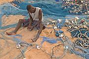 Fisherman repairing fishing nets on the beach at Aflao, Volta region, Eastern Ghana.