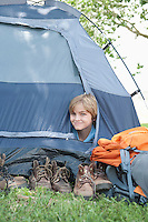 Young boy peaks out of tent
