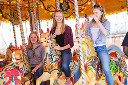 © Licensed to London News Pictures. 22/04/2018. Brighton, UK. a group of women enjoy a ride on the carrousel. Members of the public take to the beach in Brighton and Hove as warm and sunny weather continues to hit the South-east. Photo credit: Hugo Michiels/LNP