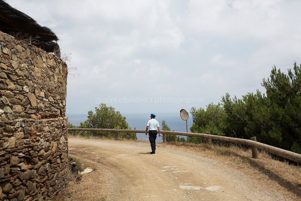 GORGONA, ITALY - 27 JUNE 2014: A prison officer walks from the farm to the one-hectare vineyard in Gorgona, Italy, on June 27th 2014.<br /> <br /> Gorgona is the smallest island of the Tuscan archipelago, located 18 miles west of Livorno, which became an experimental agricultural penal colony in 1869.<br /> <br /> The &ldquo;Frescobaldi per Gorgona&rdquo; project  provides inmates the opportunity to learn winemaking techniques and job skills under the supervision of the company&rsquo;s agronomists and winemakers, led by Vice President Lamberto Frescobaldi himself. Fifty inmates contributed to the production of Gorgona, a white wine made from Vermentino and Ansonica grapes planted on the island of Gorgona in the Tyrrhenian Sea, close to the Tuscan coast. The Frescobaldi family purchased a hectare of old vineyards and will expand with more vineyards in the upcoming months. Total production is only 2,700 bottles, but 1,000 of the bottles will reach the US market through Frescobaldi importer Folio Fine Wine Partners, in the Fall.<br /> <br /> Born in August 2012, the Gorgona initiative was financed by the Department of Penitentiary Administration and accomplished through the collaboration of the Gorgona Penitentiary's Directorate and Marchesi de&rsquo; Frescobaldi.