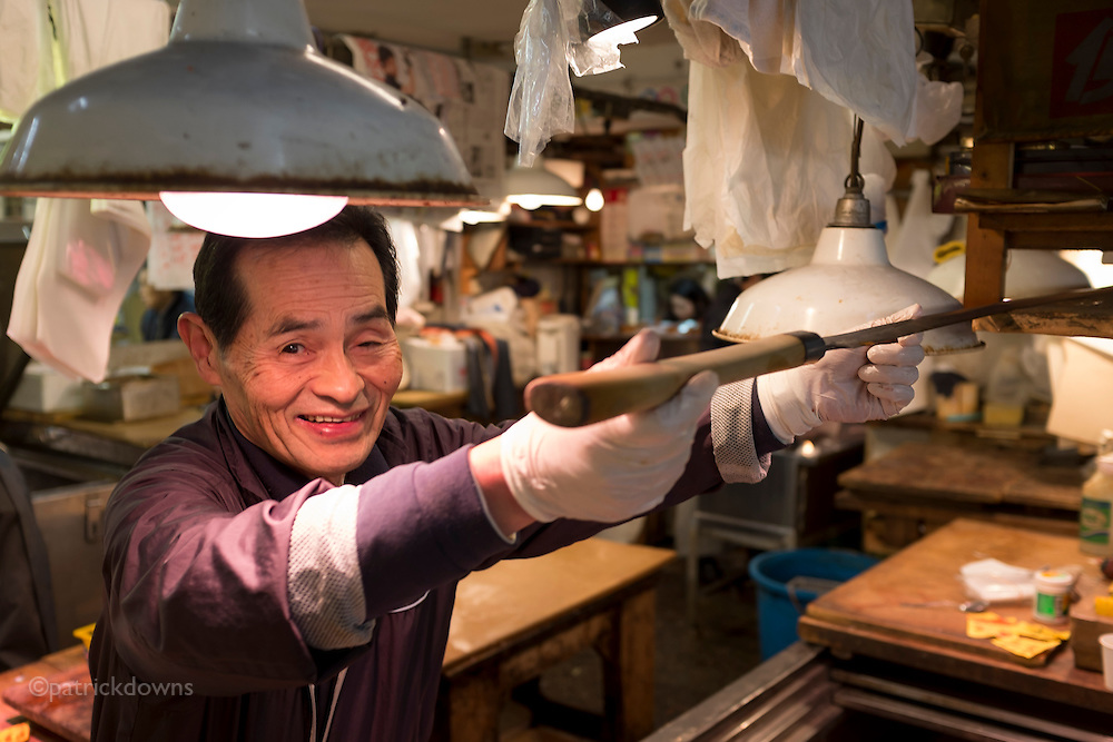 Now that's a knife! Fish monger at the famed Tsukiji Fish Market in Tokyo breaks out the big slicer to show it off.