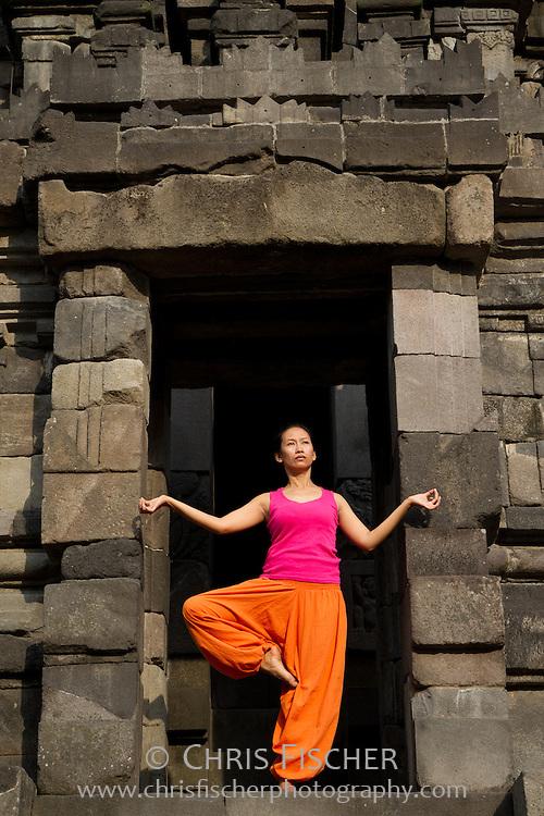 Bugis woman in traditional yoga poses at Prambanan Temple, Central Java, Indonesia.