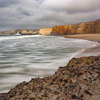 Large storm waves roll up on the beach at Yellow Bank Cliffs, near Santa Cruz, California