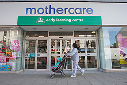 © licensed to London News Pictures. London, UK 12/04/2012. A mother with her child waiting outside Mothercare before the shop opens this morning in Wood Green on April 12, 2012. Mothercare today said it will close another 111 UK stores over the next three years in a move impacting 730 jobs. Photo credit: Tolga Akmen/LNP