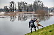 Nederland, Nijmegen, 12-1-2018Het hoogwater, hoge water, trekt veel nieuwsgierigen en andere dagjesmensen naar de Ooijpolder en levert schilderachtige beelden op. Een kunstschilder heeft zijn ezel aan de rand van het water tegen de dijk aangezet en schildert het water met de ondergelopen vegetatie en uitstekende boomtoppen.Foto: Flip Franssen