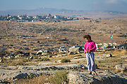 A Palestinian girl stands in front of Susiya, a small West Bank village overlooked by an illegal Israeli settlement. Like all villages in Area C of the West Bank, Susiya is under threat of demolition, ordered by Israel's Civil Administration.