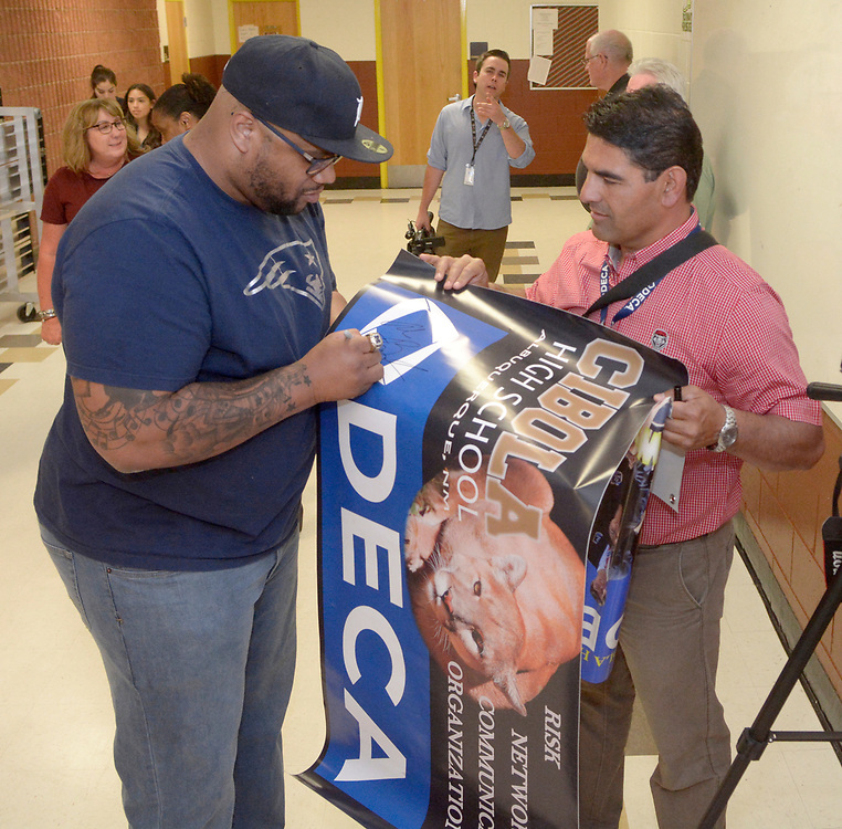 gbs050417k/SPORTS -- New England Patriots and Super Bowl Champion, Alan Branch, autographs a poster for Steven Medina with the DECA program at Cibola on Wednesday, May 3, 2017. (Greg Sorber/Albuquerque Journal)
