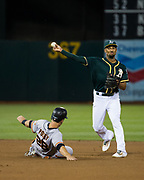 Oakland Athletics shortstop Marcus Semien (10) flips a double play against the San Francisco Giants at Oakland Coliseum in Oakland, California, on August 1, 2017. (Stan Olszewski/Special to S.F. Examiner)