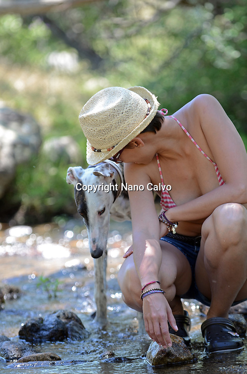 Young cute woman with her greyhound in a river