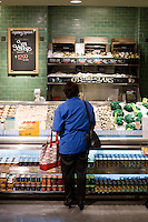 """9 July, 2008. New York, NY. Customer Tara Ramroop waits for her oysters to be shucked at the shucking station of the new Whole Foods that opened in Tribeca today, on July 9th 2008. """"I never bought them because I was never able to open them. Now I can eat them!"""" Tara Ramroop says, who lives in the neighborhood. The shucking station for oysters and clams is a new feature of the Whole Foods Market.<br /> <br /> ©2008 Gianni Cipriano for The New York Times<br /> cell. +1 646 465 2168 (USA)<br /> cell. +1 328 567 7923 (Italy)<br /> gianni@giannicipriano.com<br /> www.giannicipriano.com"""