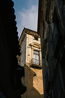 """PISCIOTTA, ITALY - 22 APRIL 2018: A view of a historical building in the historical center of Pisciotta, Italy, on April 22nd 2018.<br /> <br /> Former restaurant owners Donatella Marino and her husband Vittorio Rimbaldo have spent the recent years preparing and selling salted anchovies, called alici di menaica, to a growing market thanks to a boost in visibility from the non-profit Slow Food.  The ancient Menaica technique is named after the nets they use brought by the Greeks wherever they settled in the Mediterranean. Their process epitomizes the concept of slow food, and involves a nightly excursion with the special, loose nets that are built to catch only the larger swimmers. The fresh, red anchovies are immediately cleaned and brined seaside, then placed in terracotta pots in between layers of salt, to rest for three months before they're aged to perfection.While modern law requires them to use PVC containers for preserving, the government recently granted them permission to use up to 10 chestnut wood barrels for salting in the traditional manner. The barrels are """"washed"""" in the sea for 2-3 days before they're packed with anchovies and sea salt and set aside to cure for 90 days. The alici are then sold in round terracotta containers, evoking the traditional vessels that families once used to preserve their personal supply.<br /> <br /> Unlike conventional nets with holes of about one centimeter, the menaica, with holes of about one and half centimeters, lets smaller anchovies easily swim through. The point may be to concentrate on bigger specimens, but the net also prevents overfishing."""