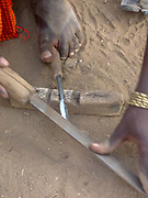 Sharpening an iron spear head made by the Gidonwoduk tribe, the former Datoga blacksmith tribe. Today they are a separate tribe. They do not marry with Datoga since they discovered the secrets of blacksmithing. Photographed in Africa, Tanzania, Lake Eyasi