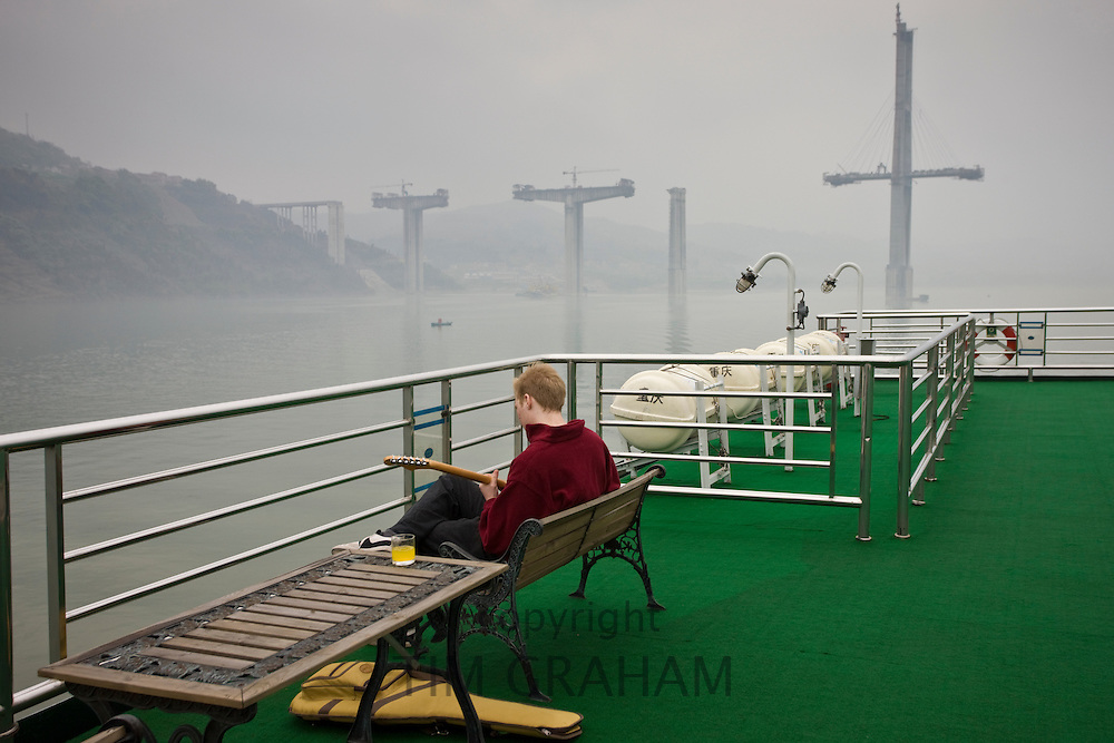 Tourist plays guitar on deck of Victoria Line Cruise Ship, Yangtze River, China