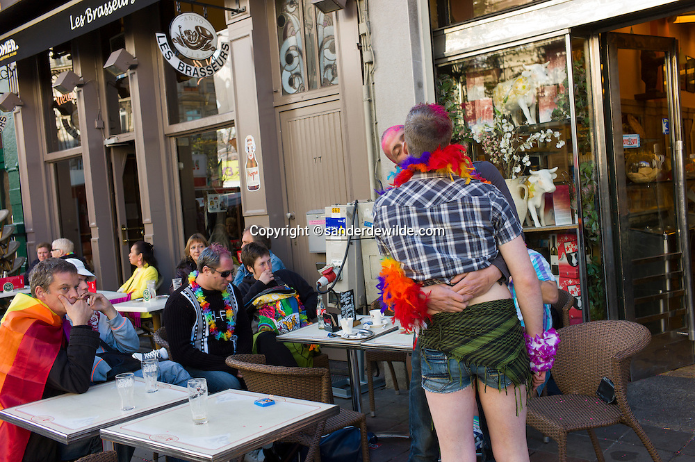 Participants of a gay pride parade in Brussels kissing. Two men kiss each other while others drink a coffee in the center of Brussels.