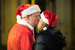 """© Licensed to London News Pictures . 17/12/2016 . Manchester , UK . A man and woman dressed as Santa Claus share a kiss , on Deansgate . Revellers out in Manchester City Centre overnight during """" Mad Friday """" , named for being one of the busiest nights of the year for the emergency services in the UK . Photo credit : Joel Goodman/LNP"""