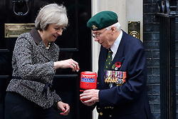©  London News Pictures. 31/10/2016. London, UK. British prime minister THERESA MAY places a £10 nite in the charity box as she meets veterans involved in the Royal British Legion on the steps of 10 Downing Street to donate to the Poppy Appeal. The Poppy Appeal raises funds for the armed forces  by selling red poppies that are worn around remembrance Sunday, to remember fallen Service men and women killed in conflict. Photo credit: Ben Cawthra/LNP