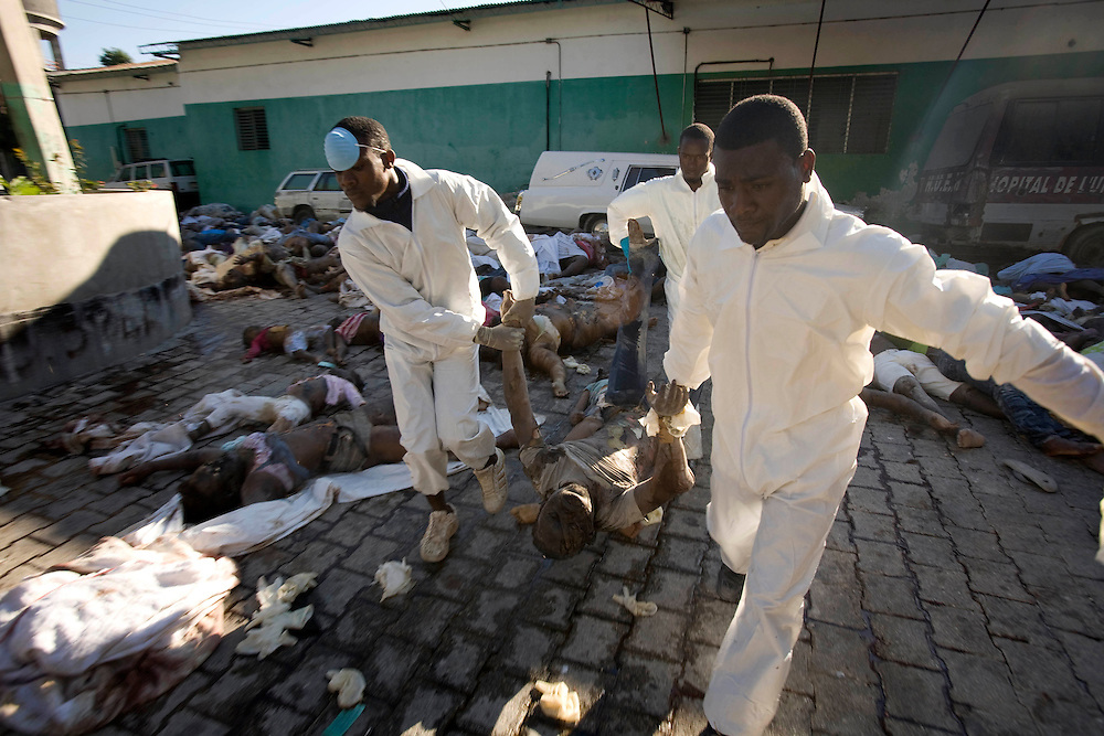 More bodies are brought to the street at the General Hospital in downtown Port-au-Prince to transport them to a common grave in Haiti on Friday January 15, 2010.