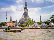 "05 OCTOBER 2012 - BANGKOK, THAILAND:   A long tail boat passes Wat Arun, the ""Temple of the Dawn"" on the Chao Phraya River. Wat Arun is one of the most famous temple in Thailand. Its Khmer style ""prang"" dominates the skyline of this part of Bangkok.     PHOTO BY JACK KURTZ"