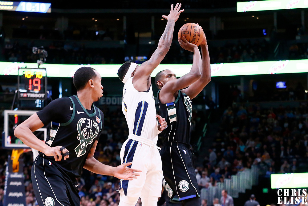 01 April 2018: Milwaukee Bucks forward Khris Middleton (22) takes a jump shot past Denver Nuggets guard Torrey Craig (3) on a screen set by Milwaukee Bucks center John Henson (31) during the Denver Nuggets 128-125 victory over the Milwaukee Bucks, at the Pepsi Center, Denver, Colorado, USA.