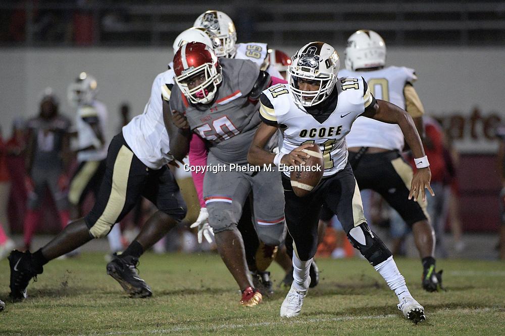 Ocoee quarterback Myles Holder (11) scrambles away from Edgewater defensive lineman Manson Clayton (50) during the second half of a high school football game Monday, Oct. 9, 2017, in Orlando, Fla. Edgewater won 44-29. (Photo by Phelan M. Ebenhack)