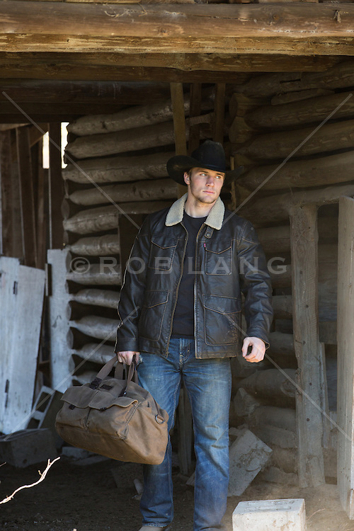 cowboy with a duffle bag walking out of a rustic barn