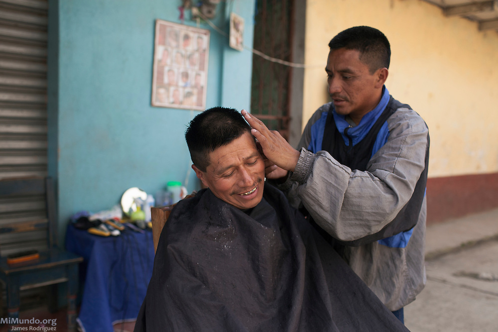 Andres Francisco (left) gets his haircut from Jesus Domingo Miguel who carries out his outdoor business on a side alley near the market. San Miguel Acatán, Huehuetenango, Guatemala. November 2, 2012.