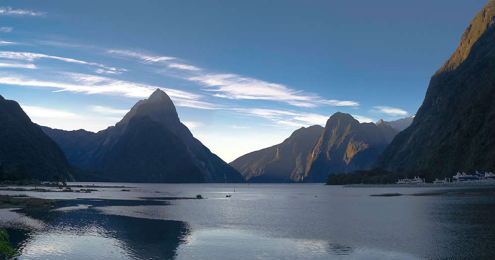 A panoramic view of Milford Sound at sunset, with Mitre Peak left of center.