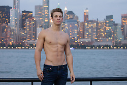 shirtless muscular man by the Hudson River overlooking the New York City Skyline