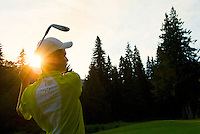 A young man hits a wedge golf club to a perfect pitch onto the golf green at sunset.
