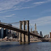 Brooklyn Bridge with the city skyline behind as seen from the East River