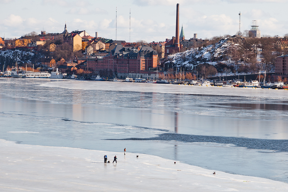 Fishing on the the frozen Lake Mälaren, Riddarfjärden, in Stockholm.  The background is Södermalm.