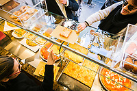 NAPLES, ITALY - 4 JANUARY 2019: Customers order street food at the street food counter of Janarius, a restaurant in Naples, Italy, on January 4th 2019.<br /> <br /> Janarius is a typical Neapolitan gourmet restaurant and shop founded by Francesco Andoli in September 2018 in via Duomo, in front of the Naples's Duomo and treasure of Saint Janarius.