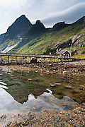 Sharp mountains at Vindstad on Moskenesøya (Moskenes Island) rise above Reinefjord in the Lofoten archipelago, Nordland county, Norway, Europe.