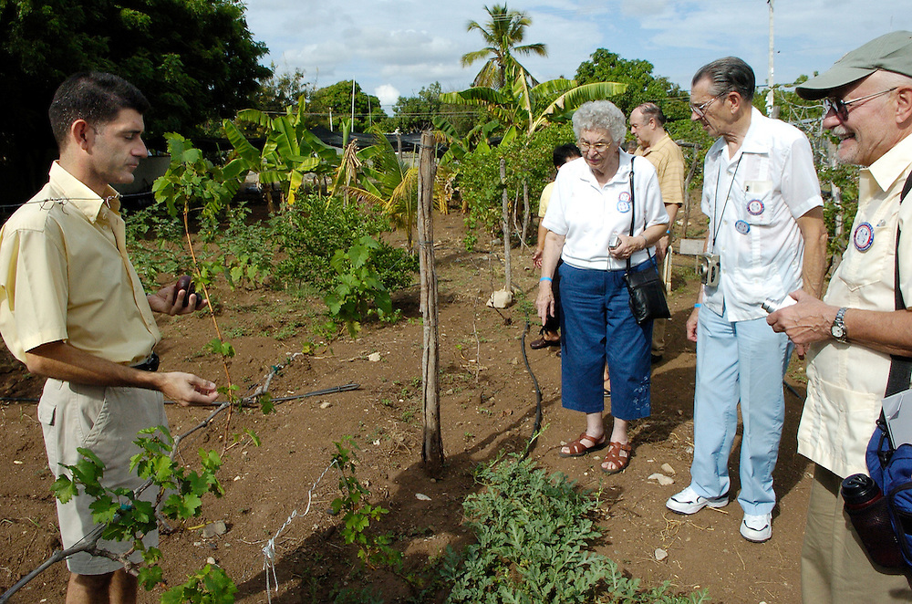 Visitors from the Milwaukee Archdiocese listen to Fr. Marti Colom describe the experiemental garden created behind the parish rectory in Sabana Yegua. The garden includes grape vines, which some day may become a new crop for local farmers.<br />