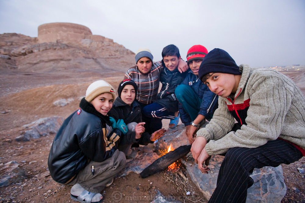 Iranian boys sit around a fire near the abandoned Zoroastrian towers of silence in the city of Yazd, Iran.  Zoroastrians brought their dead to towers of silence, where their bodies would be eaten by birds before the practice was outlawed by the Iranian government.  The bodies of the dead were considered unclean by Zoroastrians and so corpses were put atop the towers (often hilltops) so that the earth would not be polluted by the remains. Today Zoroastrians in the community are buried in a nearby cemetery , although placed so that the body does not touch the earth.