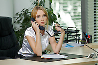 Portrait of businesswoman using phone at office