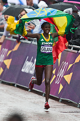 © Licensed to London News Pictures. 05/08/2012. London,UK.Tiki Gelana of Ethiopia celebrates winining gold in the Women's Marathon at the London 2012 Olympic Games Athletics, Track and Field events in London.  Photo credit : Bogdan Maran/LNP/BPA