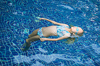 Little Girl Floating in Swimming Pool