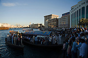 Bur Dubai. Dubai Creek. Abras (water taxis) in front of the skyline. People pushing to get aboard during rushhour.