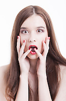 Portrait of shocked young woman with hands on face against white background