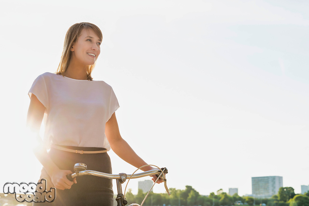 Portrait of young attractive businesswoman holding bicycle while walking on the beach