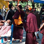 India. Bihar. Bodhgaya. Hairdresser at work on the street...shaving a customer whilst a group of  monks walks by.