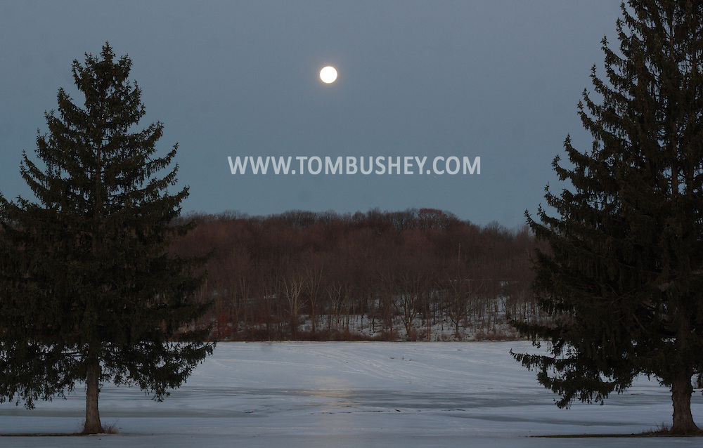 Middletown, NY  - The full moon shines between two evergreen trees on the morning of Dec. 24, 2007. The planet Mars is visible to the lower right of the moon.