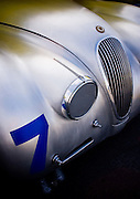Soft, classic lines and afternoon light across the silver shapes of a classic Jaguar, seen at Laguna Seca during Monterey Car Week