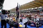 Red Bull-Renault driver Sebastian Vettel of Germany celebrates on top of his car after winning Formula One's Malaysian Grand Prix at Sepang on April 10, 2011.