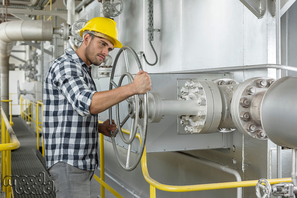 Industrial worker turning large valve