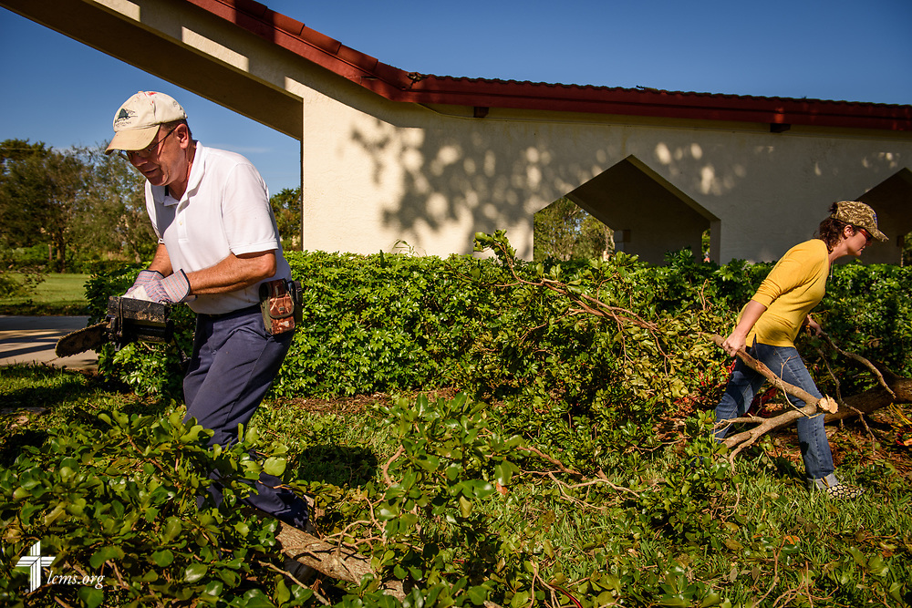 Matt Krupick (left) of Zion Lutheran Church, Fort Myers, Fla., chainsaws fallen branches leftover from Hurricane Irma at Zion on Wednesday, Sept. 13, 2017. LCMS Communications/Erik M. Lunsford