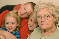 Great Grandmother sitting on the sofa with her great grandchildren,
